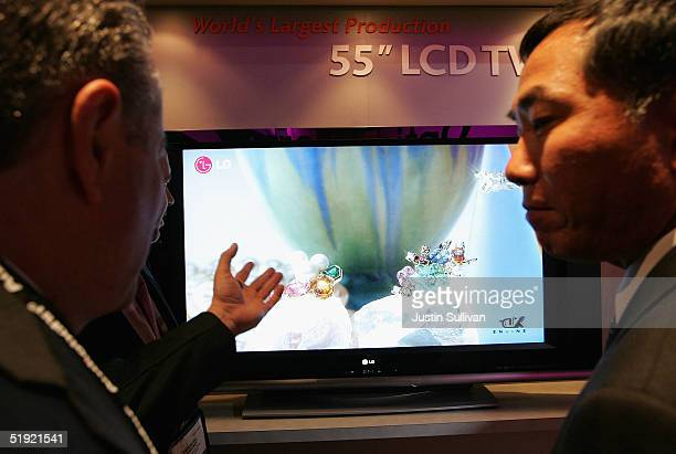 Two men look at an LG 55' LCD TV on display at the 2005 Consumer Electronics Show January 6 2005 in Las Vegas Nevada The 15 million square foot...