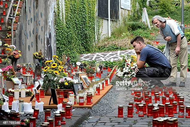 Two men look at candles and flowers left by mourners at the makeshift memorial to victims of the Love Parade disaster on its fifth anniversary on...