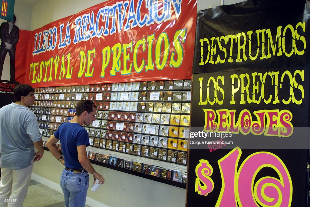 Two men look at compact discs in a music shop January 9, 2002 in Buenos Aires in one of the citys wealthiest shopping districts a day before the new Argentinan government launches an economic plan that will devaluate the peso by 40 percent.