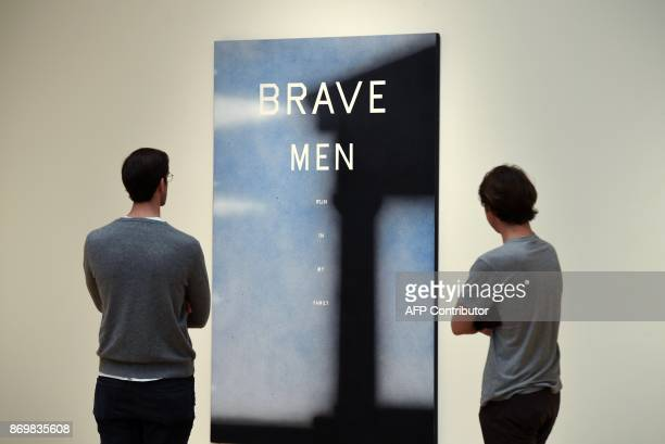 Two men look at Ed Ruscha's brave Man's Porch during a press preview at Sotheby's New York November 03 2017 for the upcoming Contemporary Art Evening...