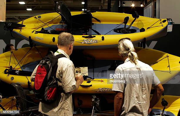 Two men look at Hobie Cat Co boats during the 2015 Outdoor Retailer Summer Market show at the Salt Palace Convention Center in Salt Lake City Utah US...
