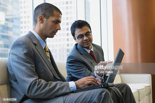 two men look at laptop in lg mod office - hitech mod a stock pictures, royalty-free photos & images