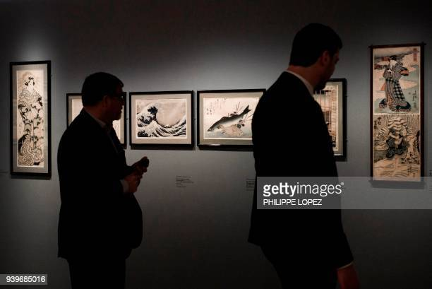 Two men look at paintings including the wave by Japanese artist Katsushika Hokusai during a preview of the exhibition Japonisms/Impressionisms at the...