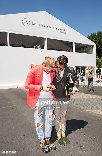 Two men look at the mobile phone during the MercedesBenz Fashion Week Berlin Spring/Summer 2016 at Brandenburg Gate on July 7 2015 in Berlin Germany