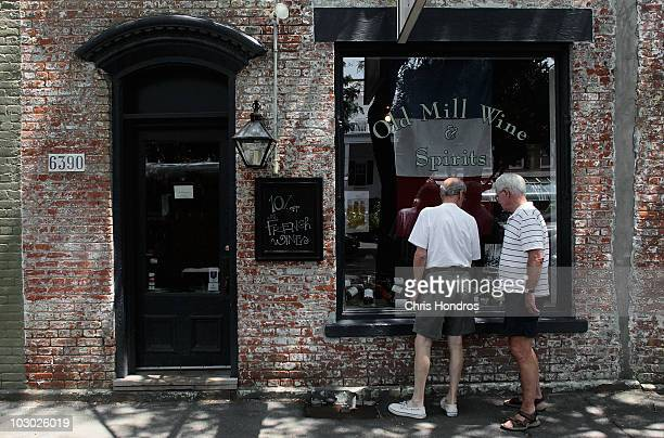 Two men look inside a wine shop display window July 21, 2010 in Rhinebeck, New York. Chelsea Clinton, the daughter of former US president Bill...