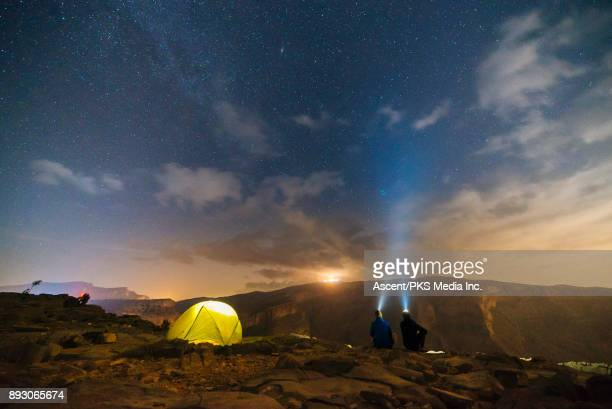 Two men look into night sky from desert camp
