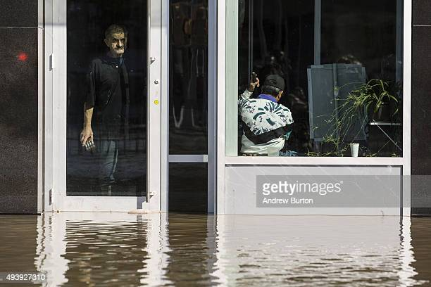 Two men look out at a flooded street from inside a shop near the site of a water main break on October 23 2015 in the Elmhurst neighborhood of the...
