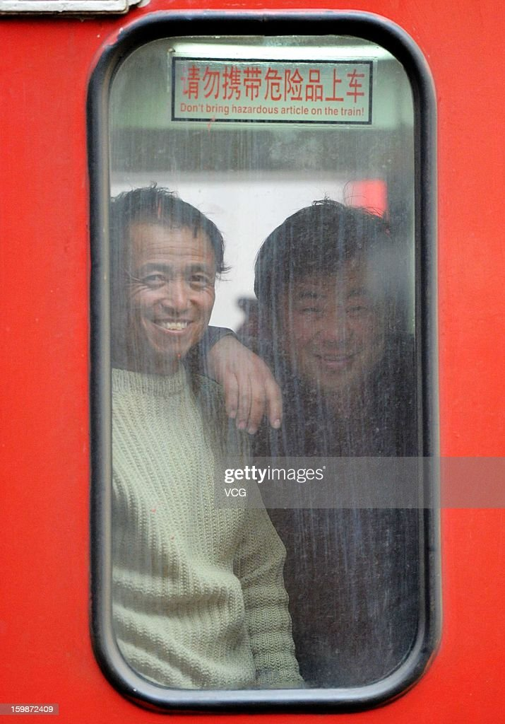 Two men look out of the window of a train at Hangzhou Railway Station on January 22, 2013 in Hangzhou, China. China's annual Spring Festival travel rush will start on January 26 as authorities estimate 3.4 billion passenger journeys will be made for the Chinese lunar new year during the 40-day travel period.
