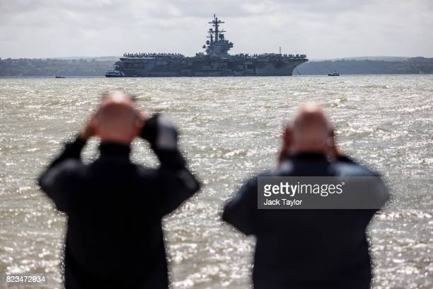 Two men look through binoculars at US Navy Nimitzclass aircraft carrier USS George HW Bush anchored off the coast on July 27 2017 in Portsmouth...