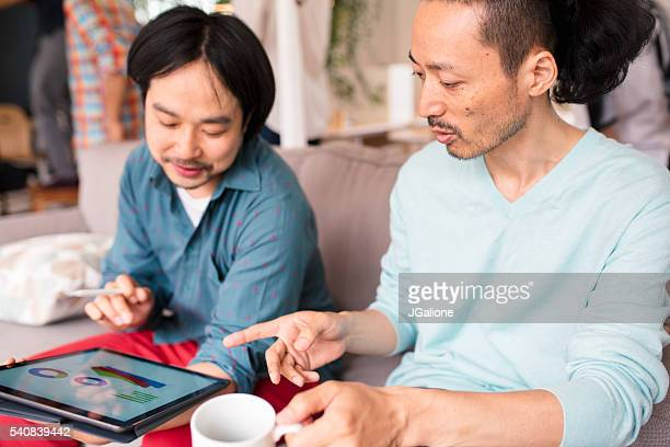 Two men looking at a digital tablet