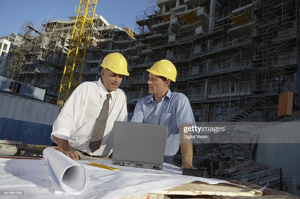 Two Men Looking at a Laptop Computer on a Building Site : Stock Photo