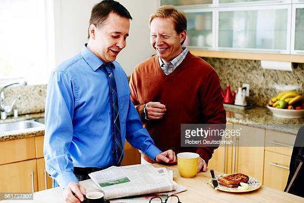 Two men looking at a newspaper with breakfast.