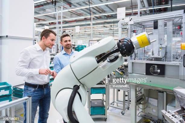 Two men looking at assembly robot in factory shop floor