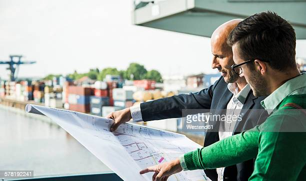Two men looking at construction plan at container harbor
