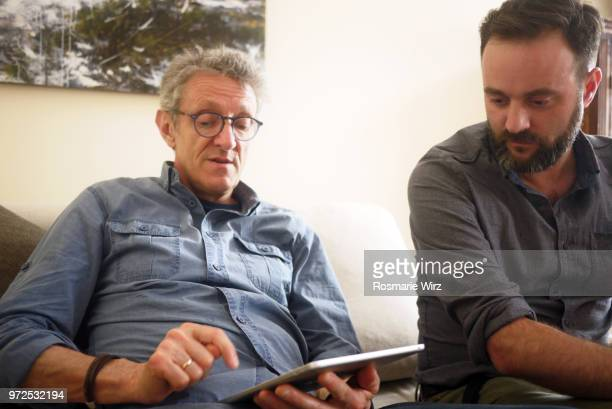 two men looking at digital tablet - southern european descent stock pictures, royalty-free photos & images