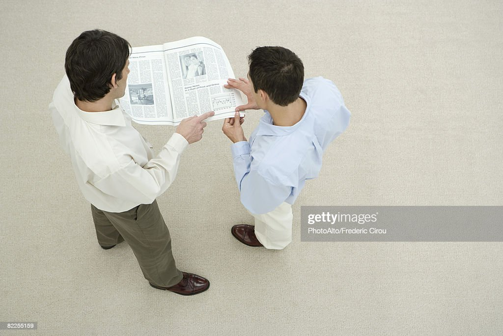 Two men looking at newspaper together, overhead view : Stock Photo