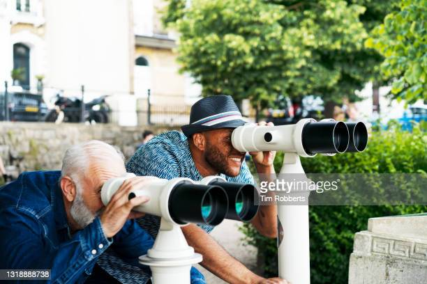 two men looking at view with binoculars - discovery stock pictures, royalty-free photos & images