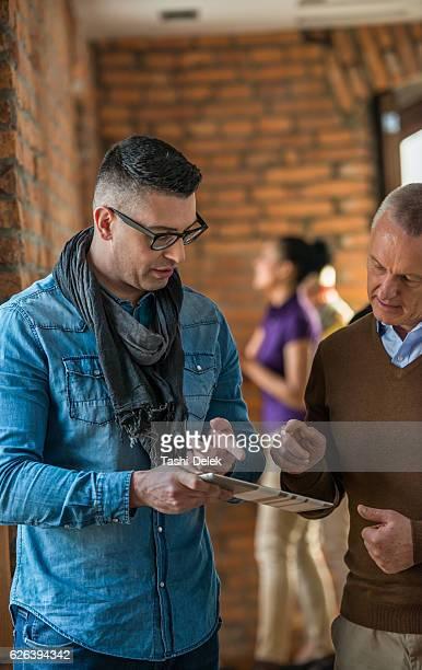 Two Men Looking In Tablet Computer