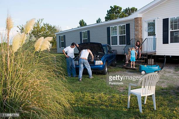 Two men looking under the hood of a pickup truck in front of trailer home