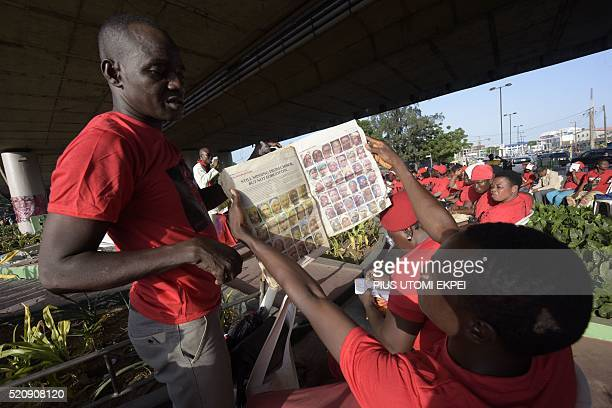 Two men looks at pictures of missing girls published in a local daily to mark the second anniversary of the 219 Chibok schoolgirls kidnapped by Boko...