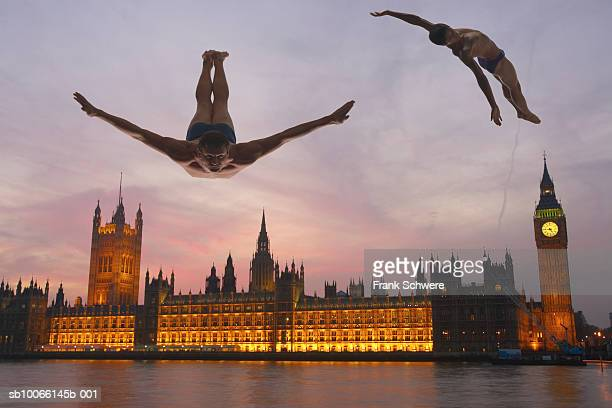 Two men lweaping and diving in front of Houses of Parliament, London, England