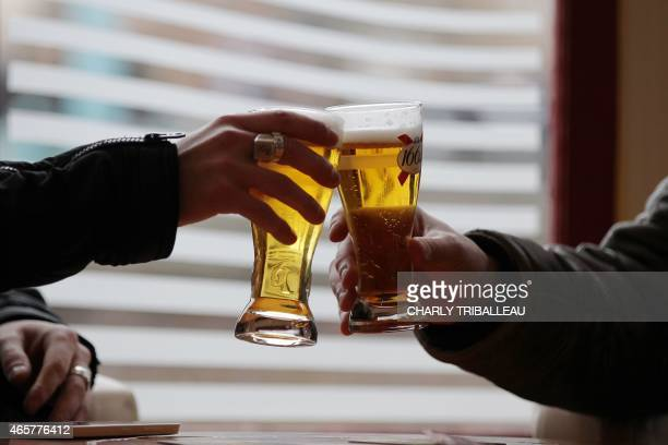 Two men make a toast prior to drink a beer at a bar table on March 10 2015 in PontAudemer northwestern France AFP PHOTO/CHARLY TRIBALLEAU