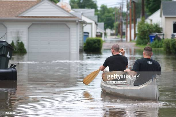 Two men make their way by canoe through the flooded streets of an evacuation zone to help those trapped June 12, 2008 in Cedar Rapids, Iowa. Much of...