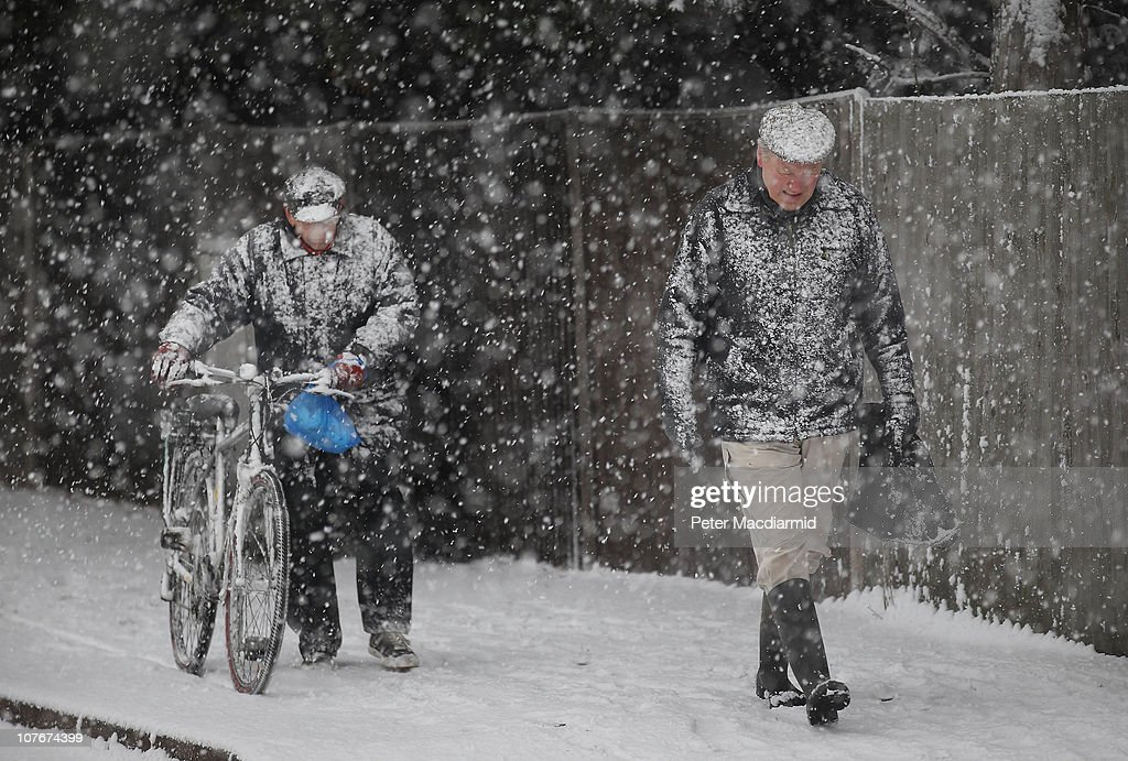 Two men make their way through a snow blizzard on December 18, 2010 in West Ewell, England. The United Kingdom is continuing to suffer heavy snowfall causing misery for travellers as it was warned there would be severe disruption to all London airports after British Airways cancelled all flights out of Heathrow until 17:00 GMT today and flights out of Gatwick between 10:00 and 16:00GMT.