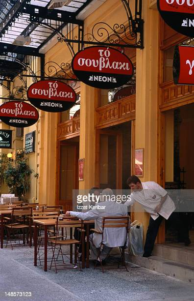 two men meet at an outdoor cafe in omonia. - men stockfoto's en -beelden