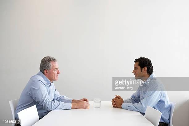 two men meeting across table - 対決 ストックフォトと画像