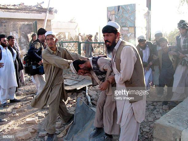 Two men mourn the death of their brother after he was killed when U.S. Jets bombed this marble tile factory overnight November 11, 2001 in Kabul,...