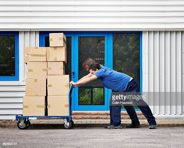 two men moving boxes on trolley