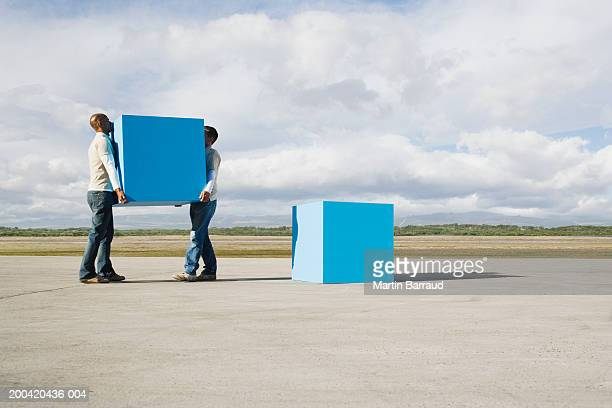 two men moving large blue blocks, side view - carrying stock pictures, royalty-free photos & images