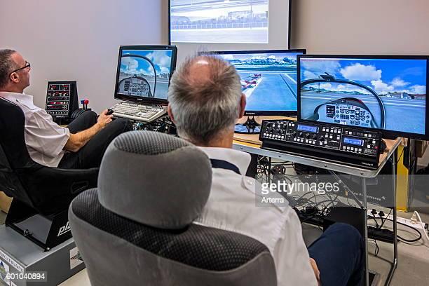 Two men navigating virtual airplane in amateur flight simulator.