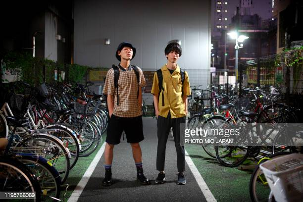 two men of millennials are hanging around the city in the midnight. - 25 29 anos imagens e fotografias de stock