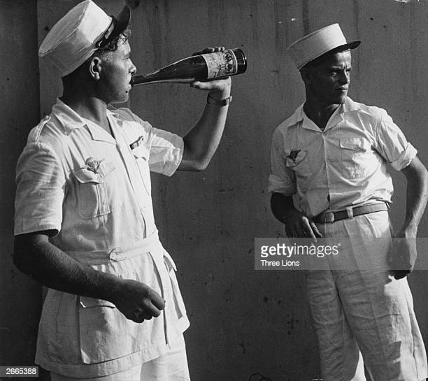 Two men of the French Foreign Legion one drinking wine from a bottle on leave in Saigon