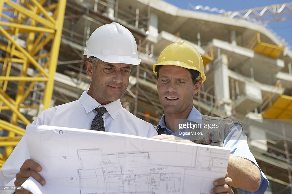 Two Men on a Building Site Looking at Blueprints : Stock Photo