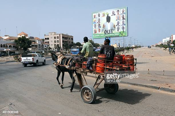 Two men on a horsedrawn cart ride past a campaign poster for incumbent Dakar Mayor Khalifa Sall with the Out written on it in a street of Dakar...