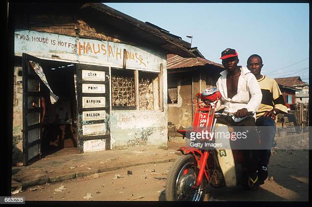 Two men on a moped drive past a barber shop December 15 1999 in the Ajegunle area of Lagos Nigeria The signs on the shop indicate that the owner is a...