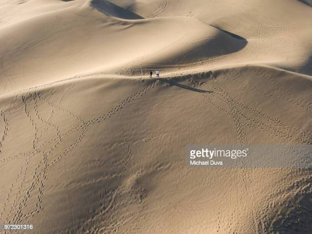 Two men on a sand dune aerial view small far away