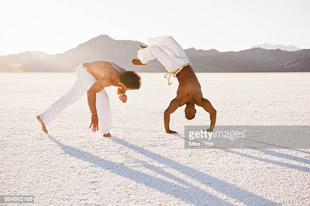 Two men on Bonneville Salt Flats performing capoeira, Utah, USA