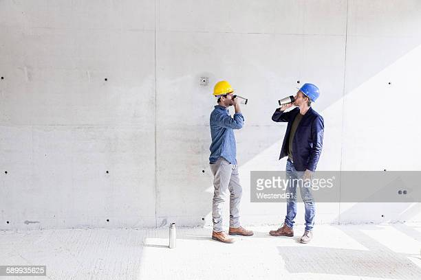 Two men on construction site drinking from mugs