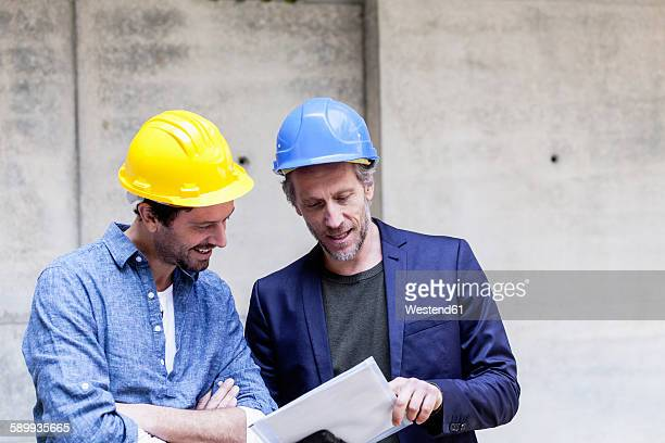 Two men on construction site looking at document