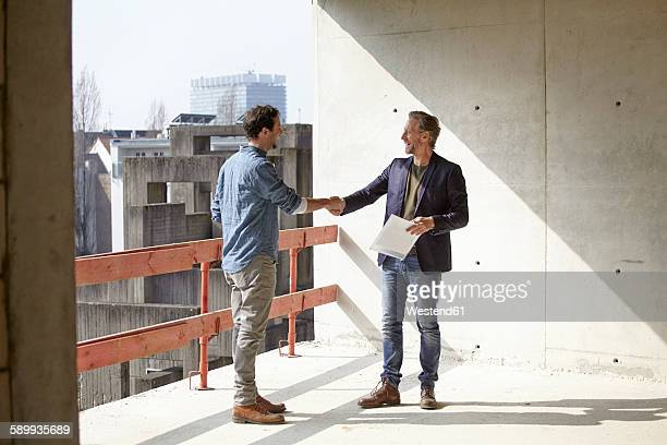 two men on construction site shaking hands - man made structure stock pictures, royalty-free photos & images