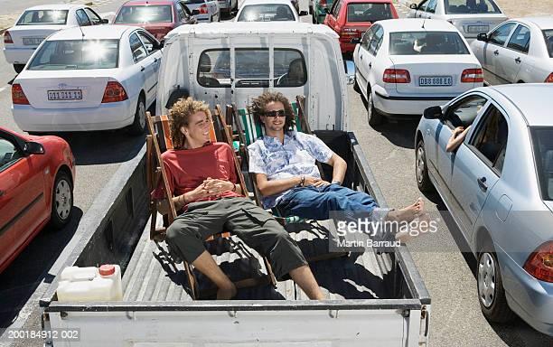 Two men on deckchairs in back of pickup truck amongst traffic jam