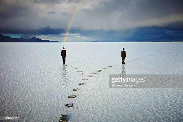 Two men on forked pathway in water under rainbow