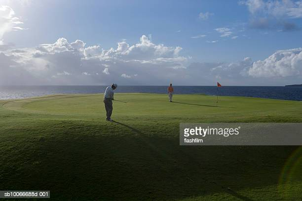 Two men on golf course, one watching and another putting golf ball