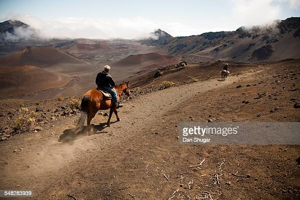 Two men on horseback ride into Haleakala crater.