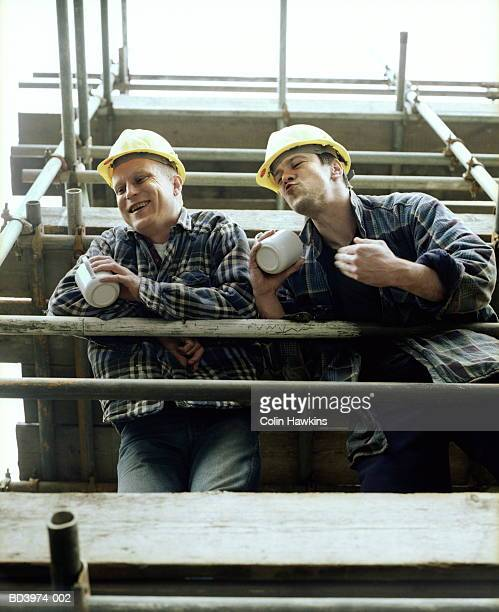 Two men on scaffolding, low angle view