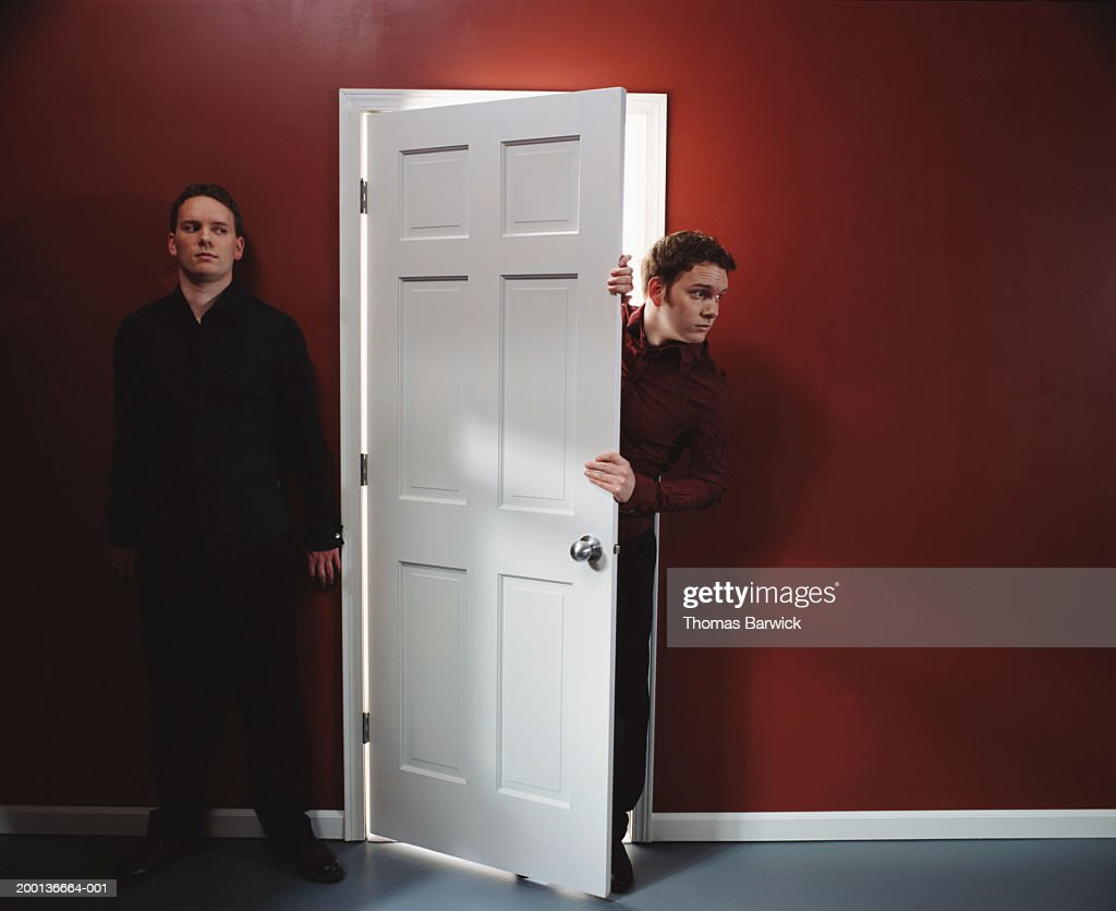Two men, one standing against wall, other peering around door : Stock Photo